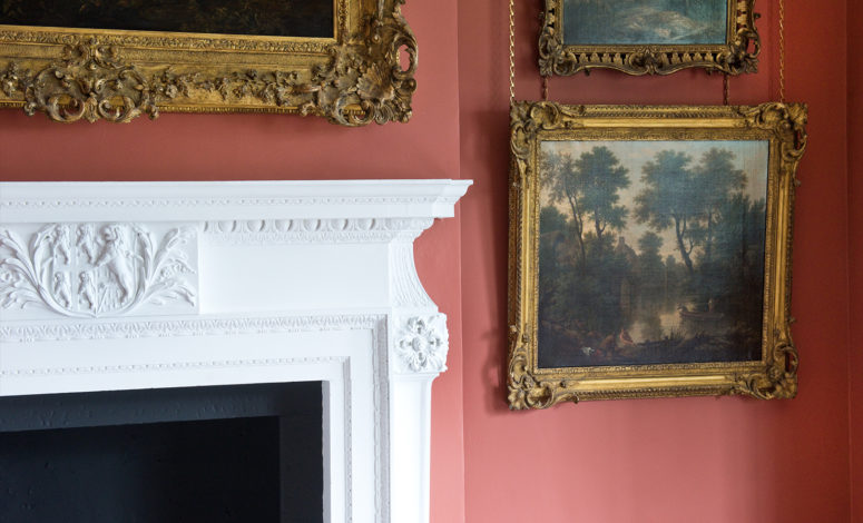 Paintings and a fireplace in the Bishop Trevor Gallery